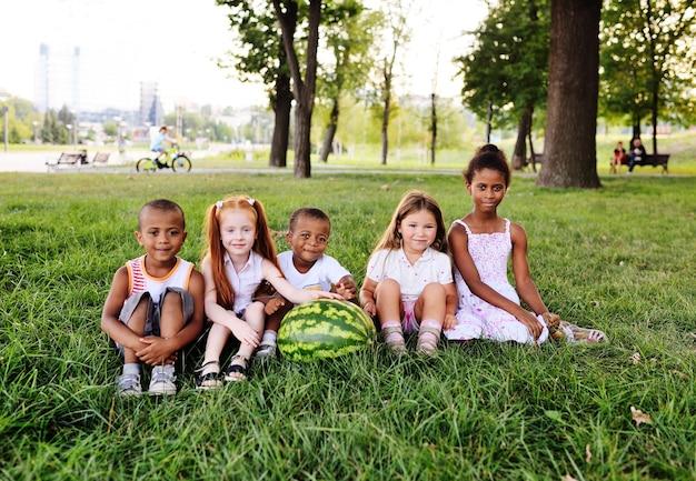 Eine gruppe von vorschulkindern im park auf dem rasen hält eine riesige wassermelone