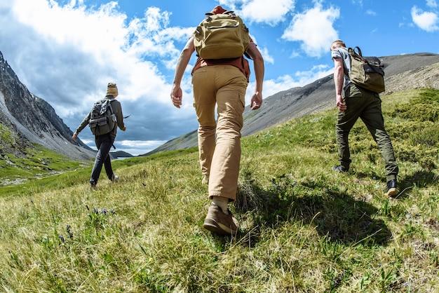 Eine gruppe von wanderern kletterer mit rucksäcken geht in die berge rückansicht