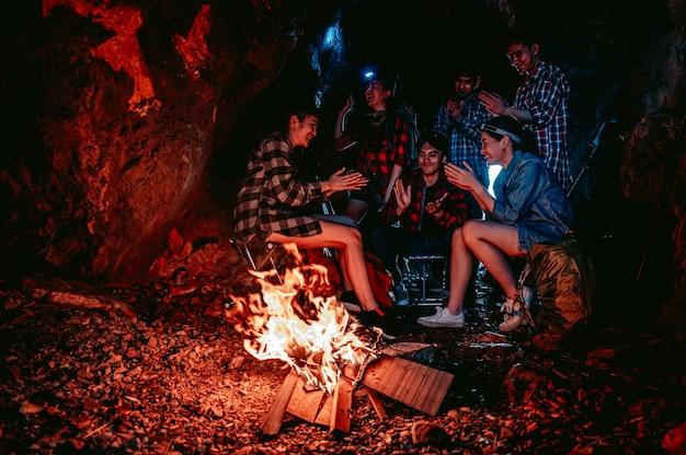 Eine gruppe von wanderern macht nachts in einer höhle ein feuer, um essen zu kochenabenteuer und campingteamwork