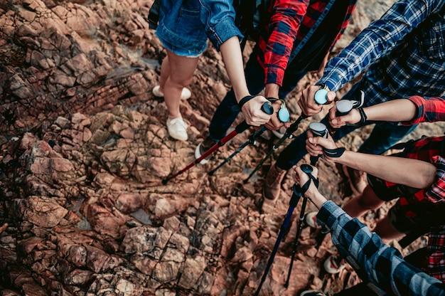 Eine gruppe von wanderern mit trekkingstöcken schließt sich als team zusammenteamwork reisen trekking erfolg