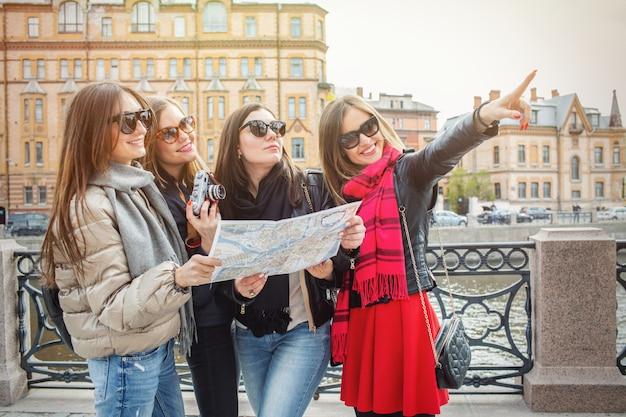 Eine gruppe von weiblichen touristen suchen auf der karte.