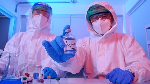 Eine gruppe von wissenschaftlern im psa-anzug erforscht den covid 19-impfstoff in einem labor.