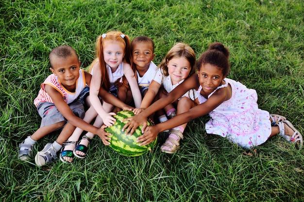 Eine gruppe vorschulkinder im park auf dem gras, das eine enorme wassermelone hält