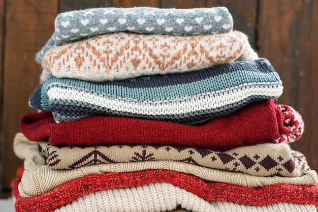 Eine gruppe warm gestrickter baumwoll- und wollpullover übereinander für die kalte jahreszeit vorbereitet