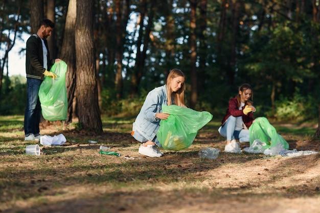Eine gruppe weiblicher und männlicher freiwilliger hält die natur sauber und sammelt müll im wald auf. naturliebhaber konzept.
