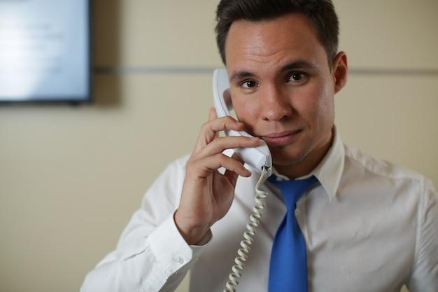 Eine gut aussehende hotelrezeption checkt den gast am telefon ein.