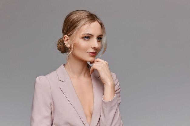 Eine gut aussehende junge frau in einem stilvollen blazer über grauem hintergrund, lokalisiert. porträt einer jungen frau mit natürlichem hautgesicht