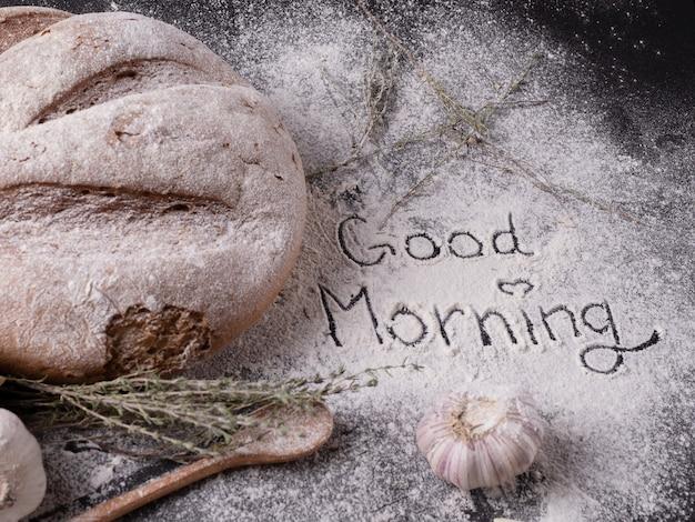 Eine gute morgeninschrift geschrieben auf backmehl nahe hausgemachtem gewürzbrot und knoblauch auf einem grauen tisch