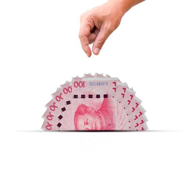 Eine hälfte der banknote chinas yuan mit der hand. yuan ist eine weltweite währung und beliebt für den austausch mit anderen.