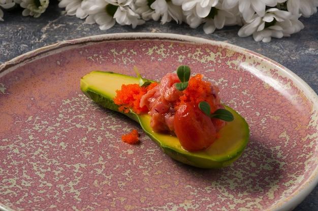 Eine halbe avocado mit lachstatar