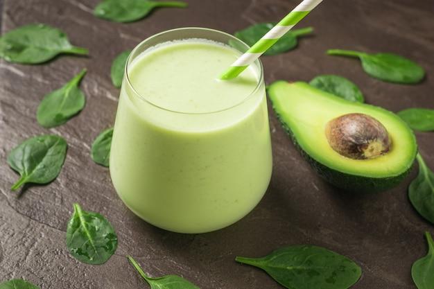 Eine halbe avocado und ein glas smoothies auf steinhintergrund mit spinatblättern. fitnessprodukt. diätetische sporternährung.