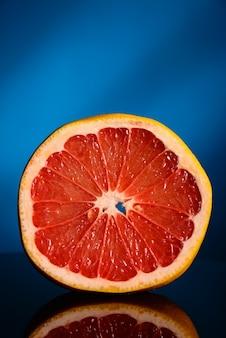 Eine halbe grapefruit lokalisiert auf blauem hintergrund