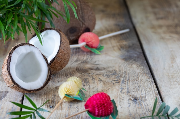 Eine halbe kokosnuss und ein palmzweig liegen auf einem holztisch. speicherplatz kopieren