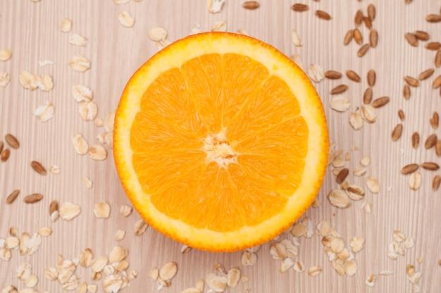 Eine halbe orange auf der tischnahaufnahme mit haferflocken und weizen auf hintergrund