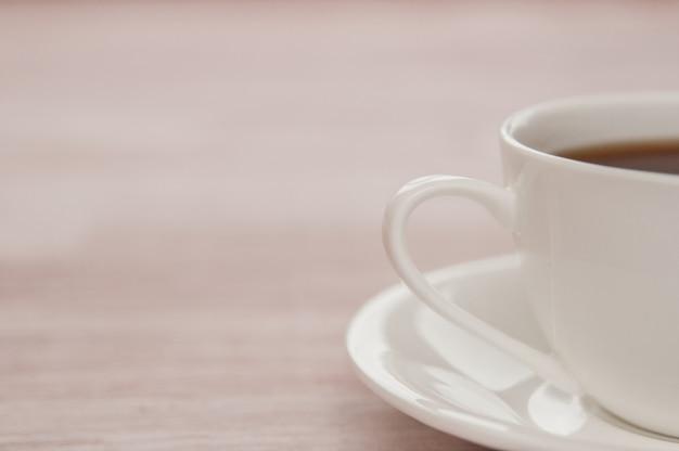 Eine halbe tasse tee auf einem hellen alten holztisch