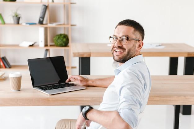 Eine halbe umdrehung erfreute büromann 30s im weißen hemd, das am tisch sitzt und kamera betrachtet, während am laptop im geschäftszentrum arbeitet