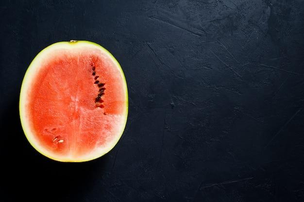 Eine halbe wassermelone auf schwarzem schiefer.
