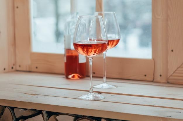 Eine halbvolle flasche roséwein und zwei gefüllte gläser stehen auf einem holzfensterbrett