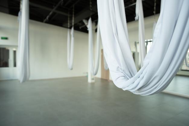 Eine halle für die ausbildung von fliegenyoga. der saal ist minimalistisch gefüllt, es gibt weiße hängematten
