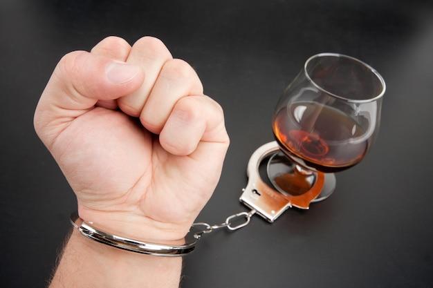 Eine hand an ein glas alkohol gebunden