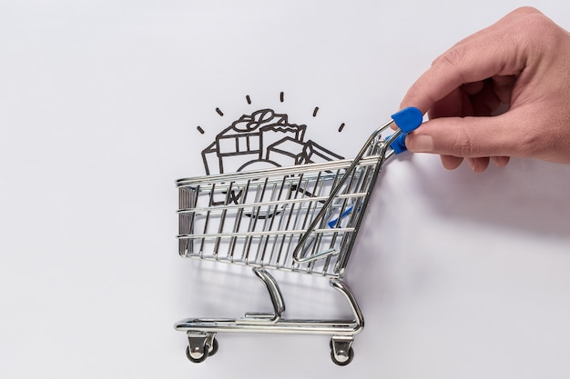 Eine hand bewegt einen minimalen einkaufswagen