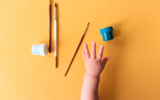 Eine hand des babys, das linien und formen mit bunten buntstiften zeichnet.