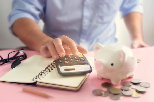 Eine hand, die auf taschenrechner-nahaufnahme für ausgabenliste mit geldmünze und sparschwein zählt. ein sparsames geld für das zukünftige investitionskonzept.