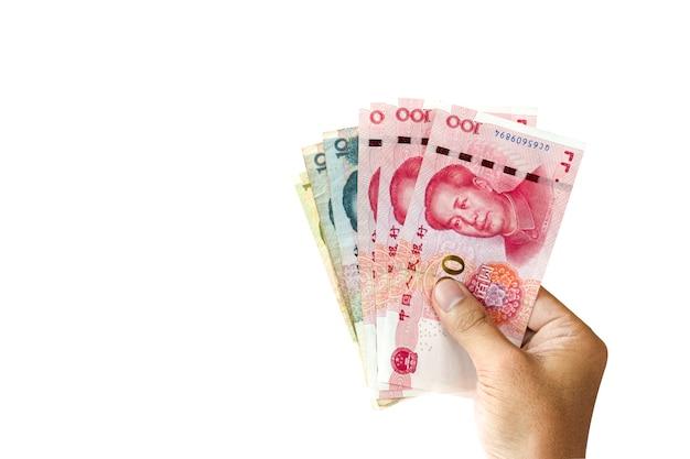 Eine hand, die banknote chinas yuan für das geben auf weißem hintergrund hält