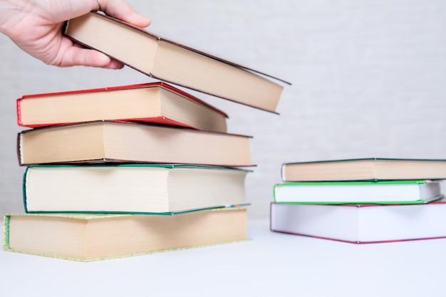 Eine hand, die ein buch von einem stapel nimmt, stapelt, bücher zum lesen und lernen auswählt und auswählt.