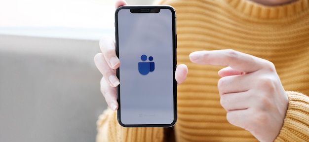 Eine hand, die ein mobiltelefon mit einem symbol von zwei personen hält