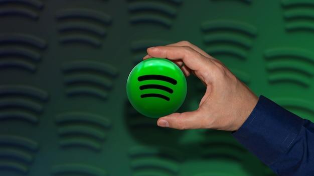 Eine hand, die ein spotify-abzeichen über einem schwarz-grünen hintergrund mit farbverlauf hält