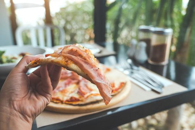 Eine hand, die ein stück parmaschinkenpizza auswählt, um im restaurant zu essen