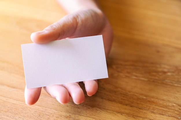 Eine hand, die eine leere visitenkarte hält und gibt