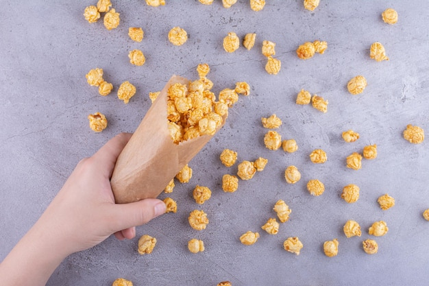 Eine hand, die eine packung karamellbeschichtetes popcorn auf marmorhintergrund verschüttet. foto in hoher qualität