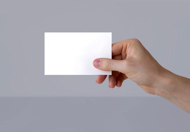 Eine hand, die eine visitenkarte hält