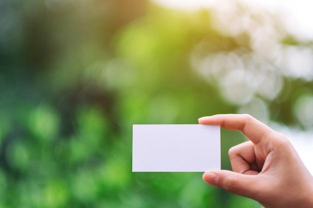 Eine hand, die eine weiße leere visitenkarte mit grünem naturhintergrund hält