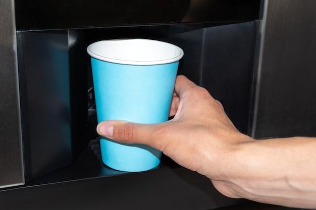 Eine hand, die einen blauen pappbecher zum einschenken eines getränks aus einem automaten hält. gießen von wasser, kaffee in einen pappbecher