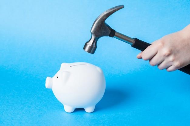 Eine hand, die einen hammer hält, der über ein weißes sparschwein angehoben wird
