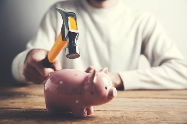 Eine hand, die einen hammer und ein sparschwein hält