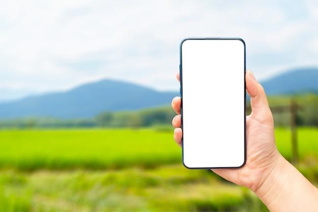 Eine hand, die einen leeren bildschirm des smartphones auf unscharf hält.