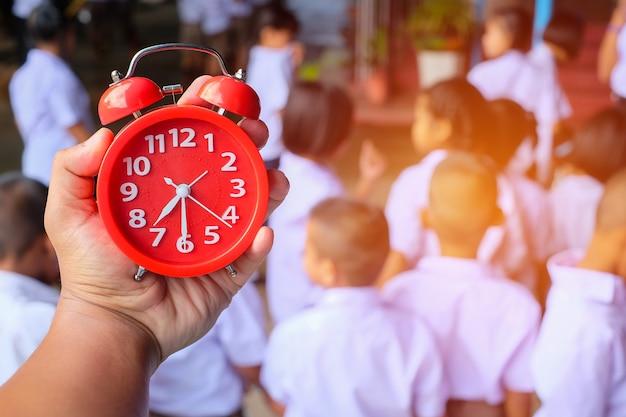 Eine hand, die einen roten wecker auf unscharfem bild des studentenclusters und des arbeitsplans an der schule in thailand hält. teamwork muss passen. zur schule gehen, nahaufnahme und unschärfe.
