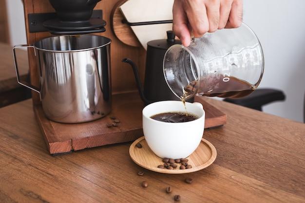 Eine hand, die filterkaffee in eine tasse gießt