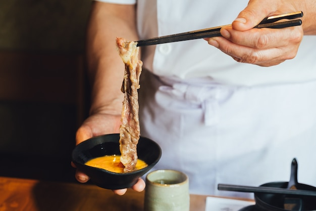 Eine hand, die gekochtes gut gemachtes scheibe wagyu-rindfleisch mit marmorbeschaffenheit klemmt