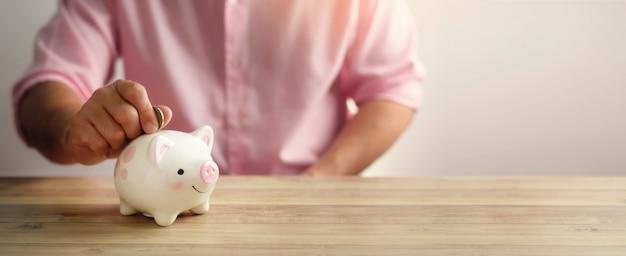 Eine hand, die geldmünze in sparschwein legt. ein sparsames geld für das zukünftige investitionskonzept.