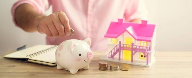 Eine hand, die geldmünze in sparschwein legt. sparen, um ein haus- oder haussparkonzept zu kaufen