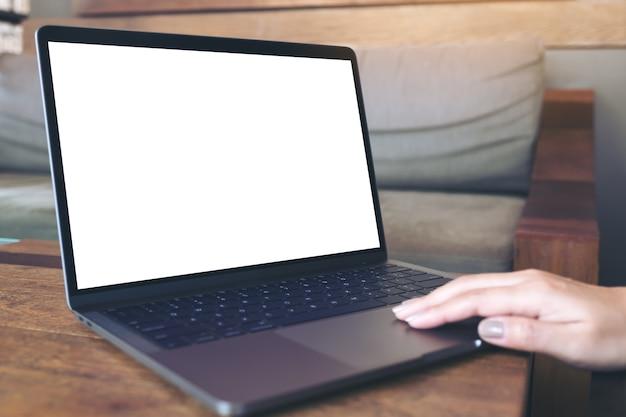 Eine hand, die laptop mit leerem weißem desktop-bildschirm auf holztisch im café verwendet und berührt