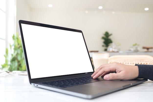 Eine hand, die laptop mit leerem weißem desktop-bildschirm auf tabelle im café schreibt und berührt