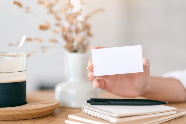 Eine hand, die weiße leere visitenkarte hält und zeigt