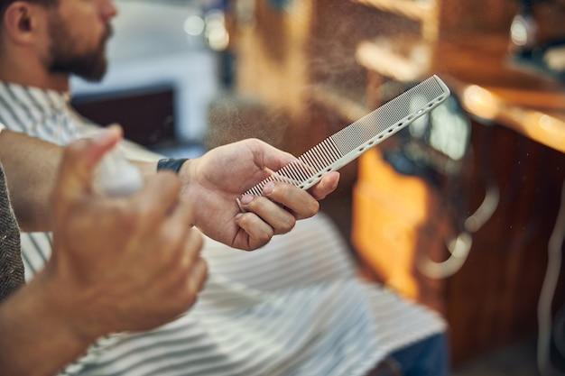 Eine hand eines friseurs, der einen haarkamm hält, während er jemandem einen haarschnitt gibt