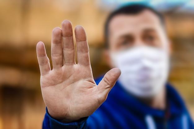 Eine hand eines mannes in einer fußmaske von einem coronavirus und luft. schutz gegen durch das virus verschmutzte pm 2.5-luft in europa und asien